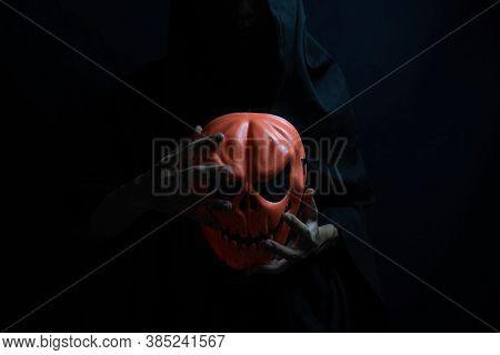 Ghost Mask In The Hands Of Satan, Dark Halloween Concept.