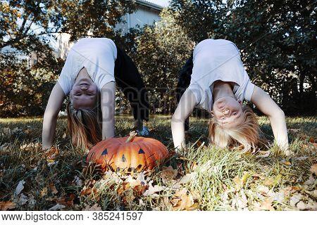 Wo Girls, Blonde Hair, Girlfriends, Next To A Large Pumpkin For Halloween. High Quality Photo