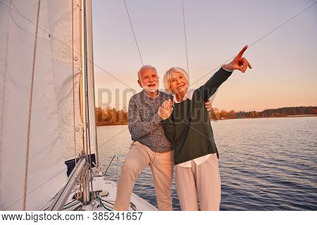 Happy Senior Couple Holding Hands And Smiling While Standing On The Side Of Yacht Deck Floating In S