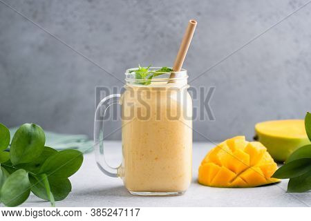 Mango Smoothie In Glass Over Grey Concrete Background. Delicious Tropical Fruit Mango Smoothie