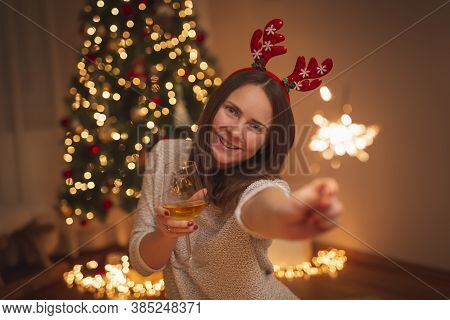 Beautiful Young Woman Wearing Deer Antlers Costume Having Fun Celebrating New Year At Home, Waving W