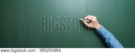 Hand Of Teacher Holding Chalk In Front Of Blank Blackboard