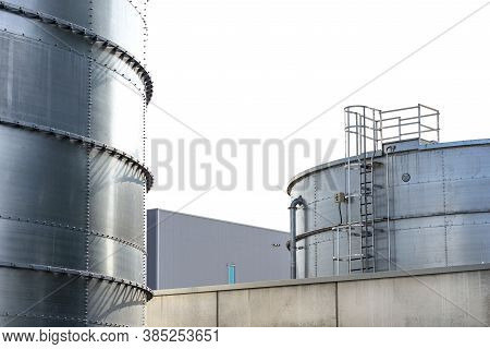 Steel Industrial Silos For Liquids And Solids Standing In A Factory Next To A Concrete Building.