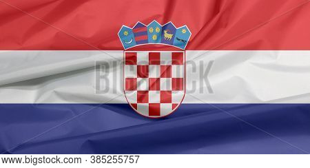 Fabric Flag Of Croatia. Crease Of Croat Flag Background, Red White And Blue With The Coat Of Arms Of