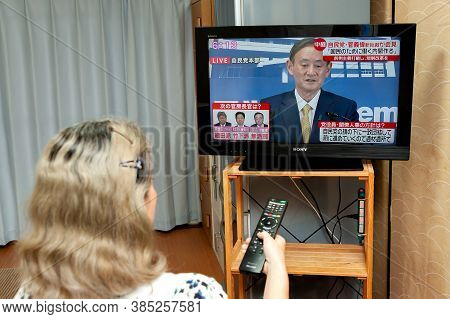 Fuji City, Shizuoka, Japan - September 14, 2020: Woman watches the press conference broadcast live on Japanese television by Yoshihide Suga, the new leader of the Liberal Democratic Party (LDP).