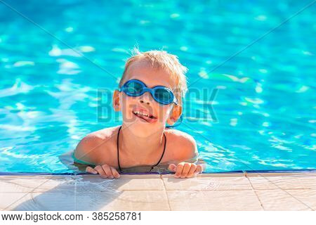 Cute Happy Little Boy In Goggles Swimming In The Swimming Pool