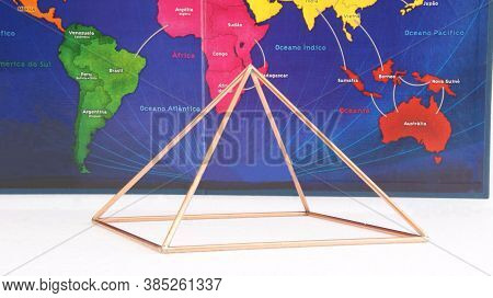 Copper pyramid. Copper pyramid in the background, cartographic representation of a world map in photo with white base