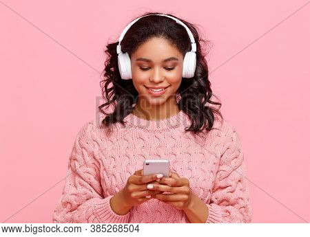 Delighted Young Ethnic Female Smiling And Browsing Social Media On Smartphone While Listening To Mus