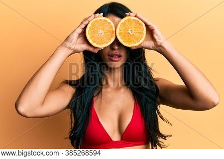 Beautiful hispanic woman wearing bikini holding orange on eyes in shock face, looking skeptical and sarcastic, surprised with open mouth