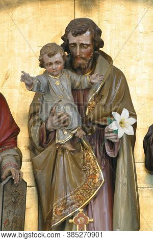 SLATINA, CROATIA - SEPTEMBER 26, 2014: Saint Joseph holds the baby Jesus, a statue on the high altar in the parish church of Saint Joseph in Slatina, Croatia