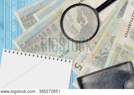5 Euro Bills And Magnifying Glass With Black Purse And Notepad. Concept Of Counterfeit Money. Search