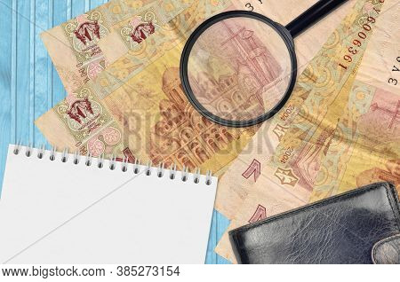 2 Ukrainian Hryvnias Bills And Magnifying Glass With Black Purse And Notepad. Concept Of Counterfeit