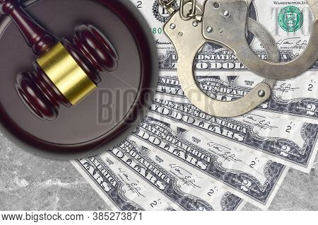 2 Us Dollars Bills And Judge Hammer With Police Handcuffs On Court Desk. Concept Of Judicial Trial O