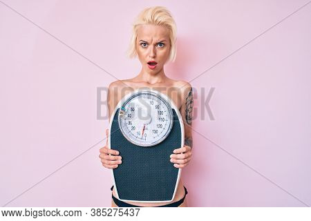 Young blonde woman with tattoo standing shirtless holding weighing machine in shock face, looking skeptical and sarcastic, surprised with open mouth