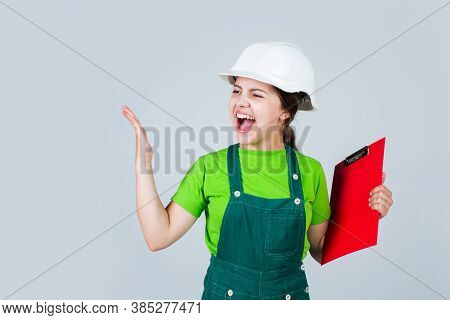 Angry Kid In Hard Hat Making Notes. Child Hold Document Folder. Kid Learn How To Be Construction Wor