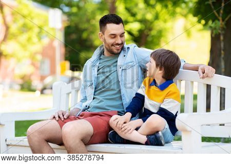 family, fatherhood and people concept - happy father and son sitting on bench at summer park and talking