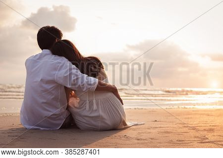 Couple In Love Watching Sunset Together On Beach Travel Summer Holidays. Romantic Couple On The Beac
