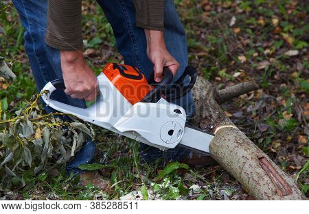 Close Up Photo Of A Lumberman With An Electric Saw Cuts A Log. Lumberjack At Work. Technique Of Work