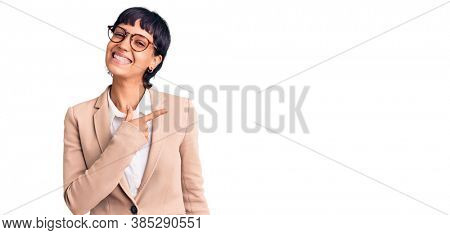 Young brunette woman with short hair wearing business jacket and glasses cheerful with a smile of face pointing with hand and finger up to the side with happy and natural expression on face
