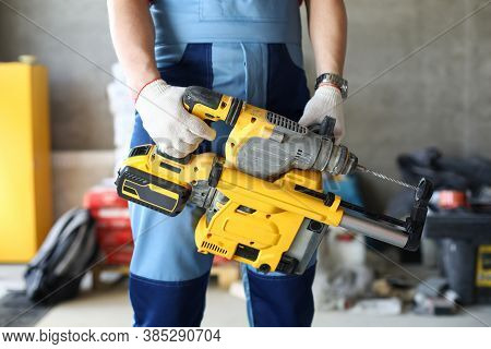 Close-up Of Perforator Tool In Hands Of Worker. Instrument Used In Construction Sites And Buildings.