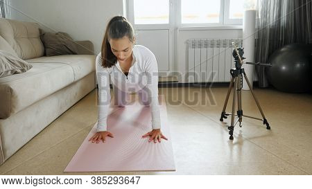 Attractive Young Female Trainer In White Sportswear Does Press Ups On Knees Shooting Video Guidance