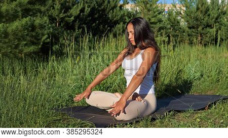 Brunette Woman Doing Asana With A Vacuum In Nature.