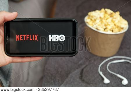 Close Up Mans Hand Holding A Mobile Phone With Netflix And Hbo Logo With Apple Earphones And Popcorn