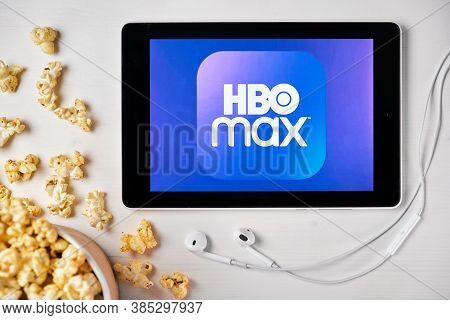 Hbo Max Logo On The Tablet Screen Laying On The White Table With Scattered Popcorn And Apple Earphon