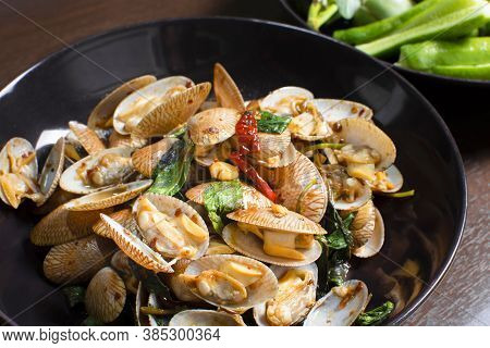 Close Up Of Stir Fried Clams With Roasted Chilli Paste In A Plate On Wooden Table