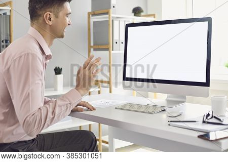 Man Using Personal Desktop Computer For Teleconference And Waving Hand During Video Call