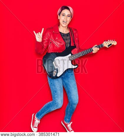 Young beautiful guitarist woman with pink short hair playing electric guitar smiling happy. Jumping with smile on face doing rocker sign with fingers over isolated red background