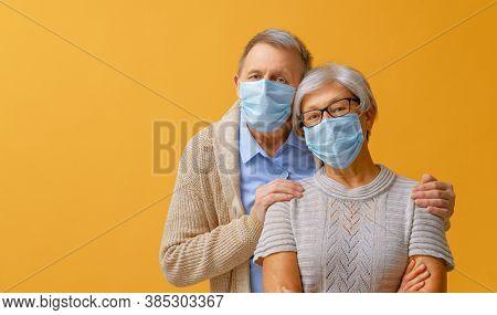 Senior couple wearing facemask during coronavirus and flu outbreak. Virus and illness protection, home quarantine. COVID-2019. Taking on masks.