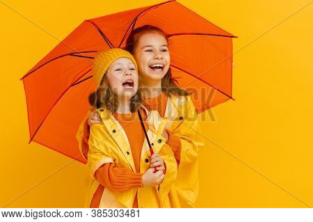 Happy emotional children laughing and embracing. Kids with orange umbrella on colored yellow background.