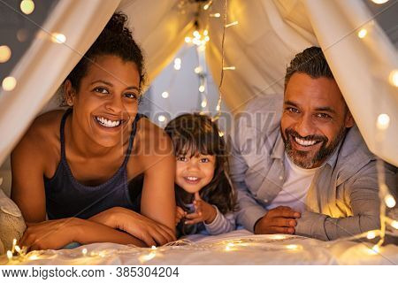 Portrait of little daughter lying with mother and father in illuminated tent. Cheerful man and happy woman lying in cozy hut with their daughter. Indian family lying on bed and having fun together.