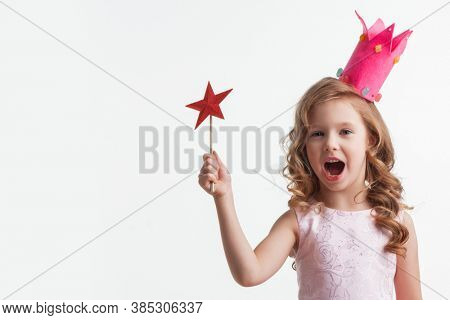 Beautiful little candy princess girl in crown holding star shaped magic wand isolated on white