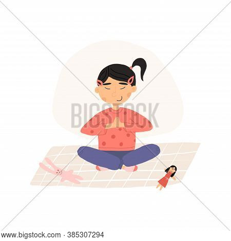 Cute Asian Girl Put Down A Toys And Meditates In Lotus Or Padmasana Pose With Her Hands Folded At Th