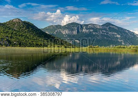 Beautiful Landscape Of Skadar (shkoder) Lake With Reflection Of Mountains And Clouds In The Water. M
