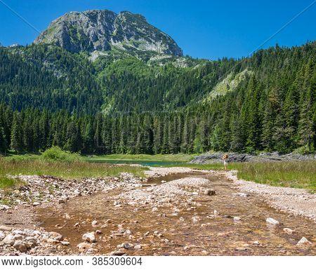 View Of The Black Lake And Mount Bobotov Kuk. National Park Durmitor, Montenegro, Europe.