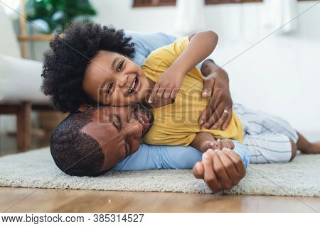 Black Father In Living Room Have A Fun Playing Together On Warm Floor At Home.happy African Family D