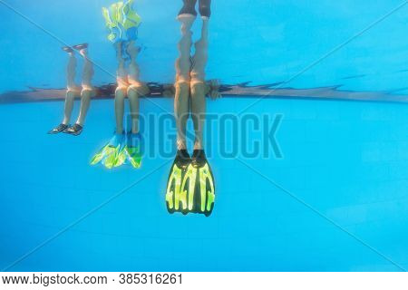 Happy People Have Fun At Pool Side Edge. Funny Photo Of Mother With Kids Legs In Fins In Aqua Park S
