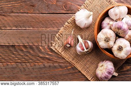 Garlic In A Plate Whole And A Clove Of Garlic On A Wooden Background, Top View. Copy Space