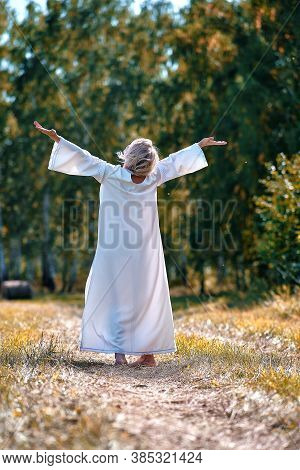 A Girl In A White Dress Pulls Her Hands To The Sun. Reuniting With Nature