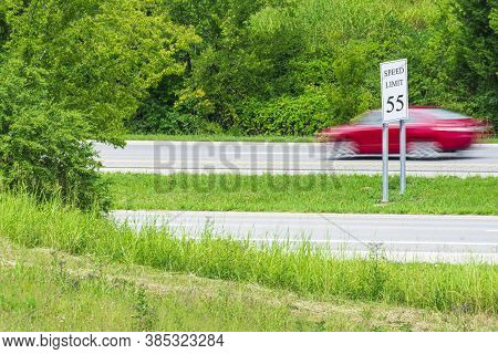 Horizontal Shot Of A Speeding Red Car Streaking By A Speed Limit Sign.  Blurring Shows Motion.