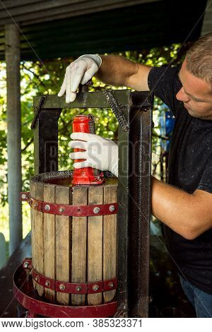 Wine Harvest. A Master Winemaker Is Setting Up A Grape Press. Freshly Squeezed Grape Juice In A Glas