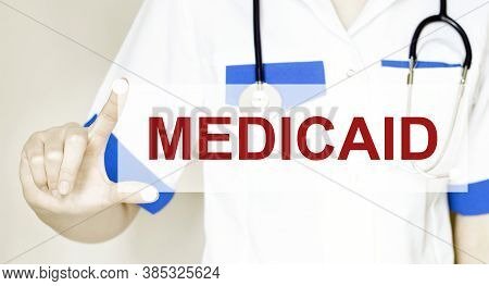 Doctor Holding A Card With Text Medicaid Medical Concept