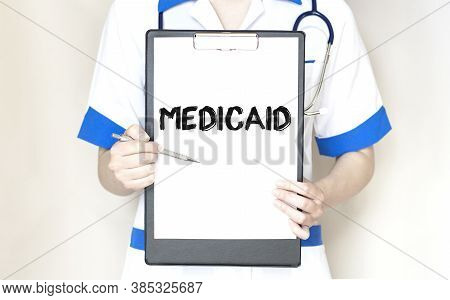 Doctor Holding A Paper Plate With Text Medicaid, Medical Concept