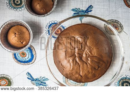 Homemade Chocolate Cake And Cupcakes On The Table. Round Baked Chocolate Cake In Glass Baking Bowl.