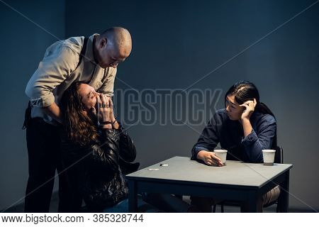 A Suspect In A Police Station Laughs Madly During An Interrogation Conducted By Investigators.