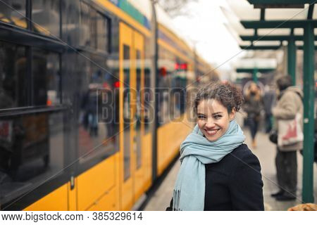 young woman takes the tram in the city