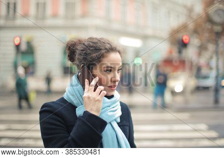 woman crosses the street while talking on the phone